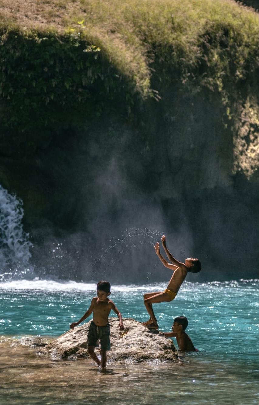Children jumping in lagoon