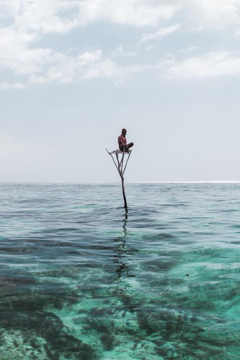 Man seating on wood pillar in Karoso lagoon