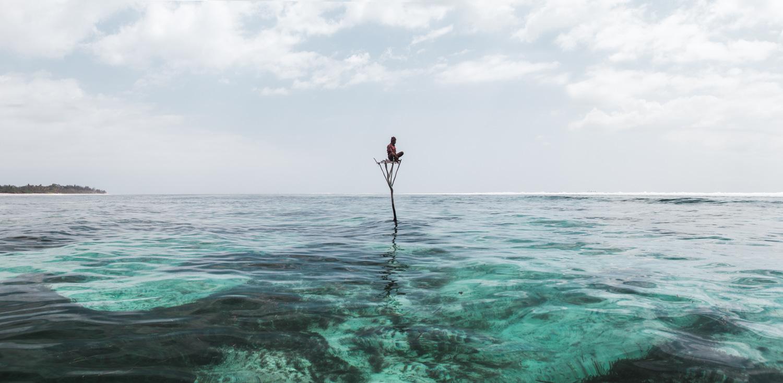 Man seated on wood pillar in Karoso lagoon