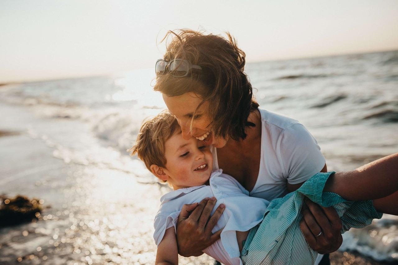 Woman holding son on beach