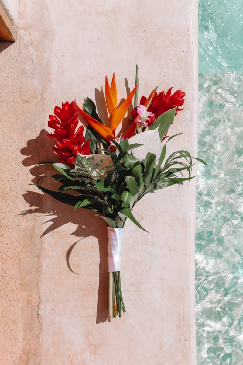 Bouquet of red and orange flowers by the side of the pool