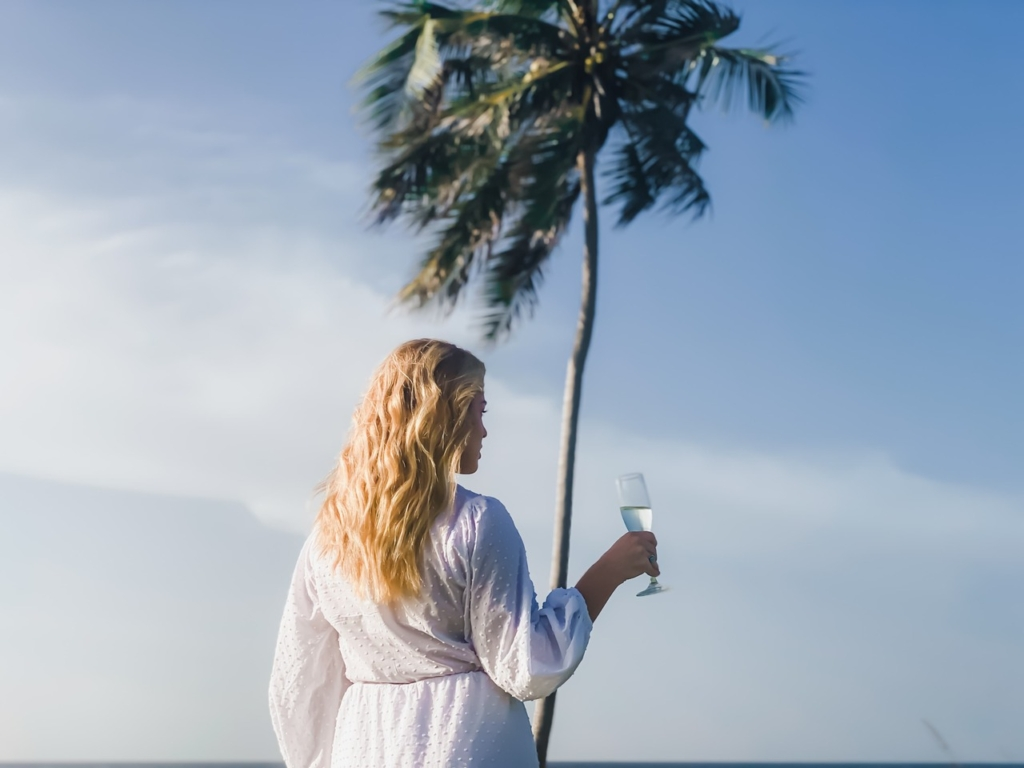 woman with a drink in hand on the beach